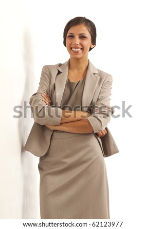 Portrait of young executive business woman wearing suit smiling with arms crossed