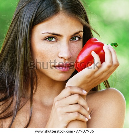 Portrait of young fair-haired woman holding Bulgarian pepper and looking somewhere at summer green park.