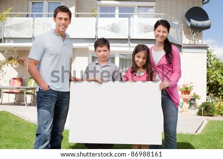 Portrait of young family holding a black white board outside their house