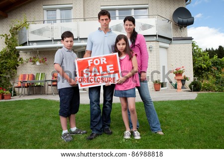 Portrait of young family holding a foreclosure sign outside their house
