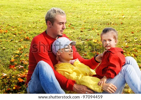 Portrait of young family on background of grass and yellow leafs