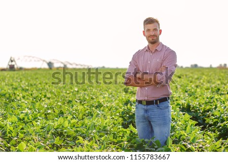 Portrait of young farmer standing in soybean field. #1155783667