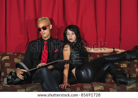 Portrait of young fashionable couple sitting on red couch with electric guitar
