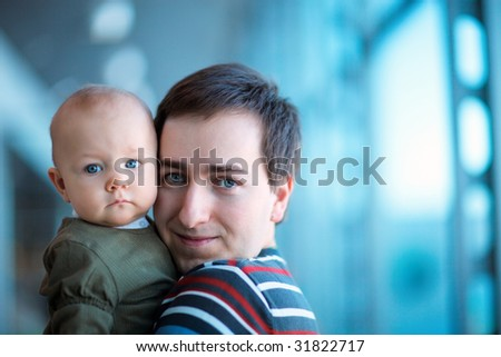 Portrait of young father and baby daughter indoors