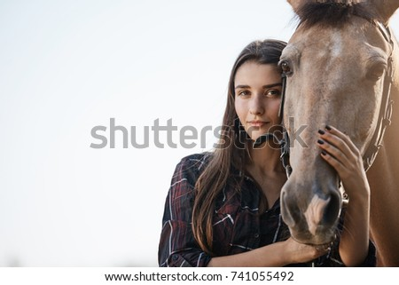 Portrait of young female assistant farm manager holding and petting a horse.