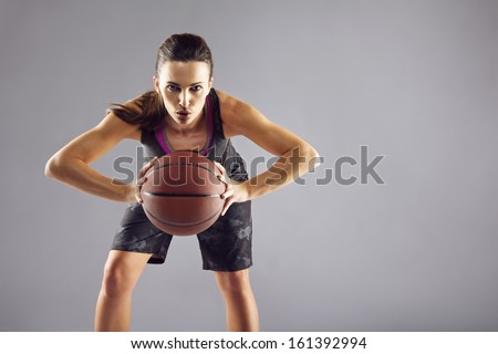 Portrait Of Young Female Basketball Player Passing The Ball. Beautiful Caucasian Woman In Sportswear Playing Basketball On Grey Background With Copyspace