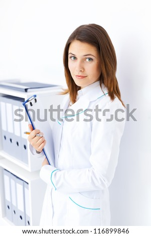Portrait of young female doctor holding clipboard in hospital