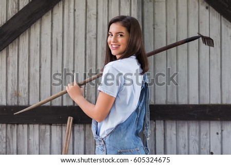 Portrait of young female farmer holding a rake over the shoulder #605324675