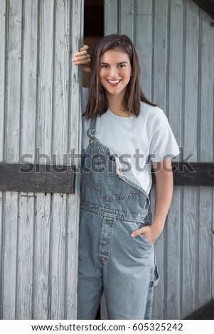 Portrait of young female farmer leaning on the door of the barn or shed #605325242