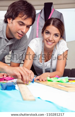 Portrait of young female fashion designer smiling while coworker draws line on fabric with chalk