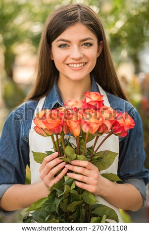 Portrait of young female florist holding bouquet with roses.