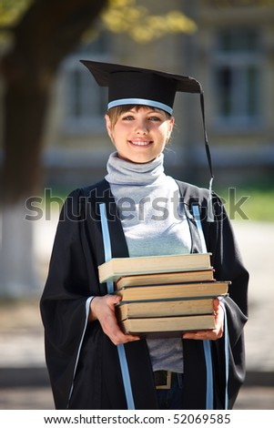 Portrait of young female graduate with stack of books, in sunlight, with blurred college building in the background