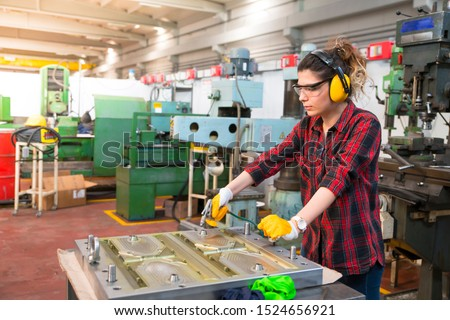Portrait of young female industry manual worker in factory
