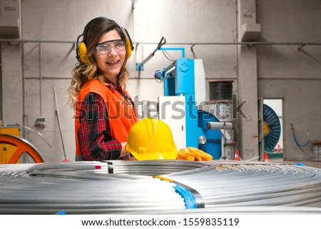 Portrait of young female industry manual worker in warehouse