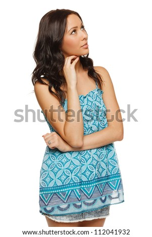 Portrait of young female looking up with interest, isolated on white background