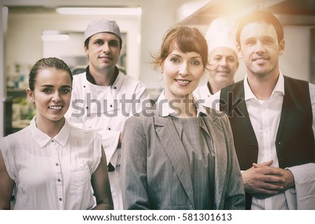 Portrait of young female manager posing in modern kitchen with staff #581301613