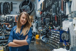 Portrait of young female mechanic in bicycle store. Stylish bicycle mechanic woman standing in her workshop. Bike service