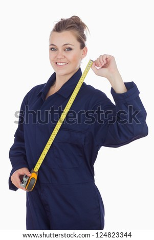 Portrait of young female mechanic with measuring tape standing against white background