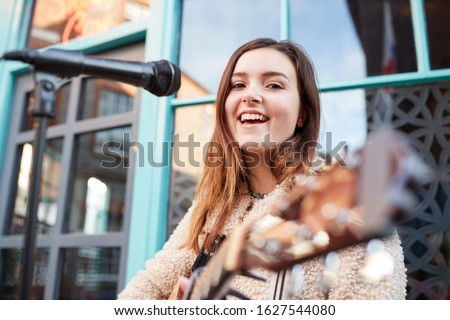 Portrait Of Young Female Musician Busking Playing Acoustic Guitar And Singing Outdoors In Street Foto stock ©