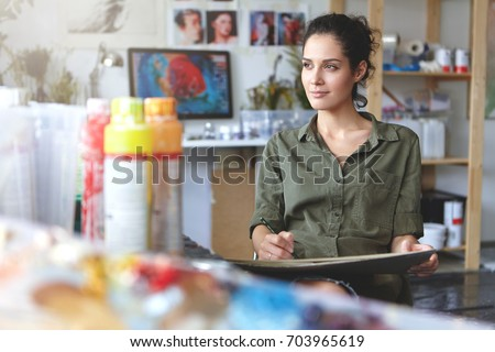 Portrait of young female of creative occupation sitting at modern workshop and working, enjoying process of creating something beautiful, looking sideways with pleased inspired expression on her face #703965619