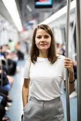 Portrait of young female passenger standing in subway car