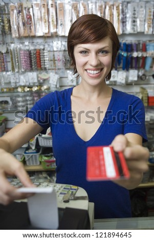 Portrait of young female sales clerk holding credit card at cash counter
