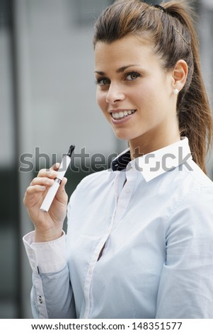 portrait of young female smoker smoking e-cigarette outdoor office building and looking at camera