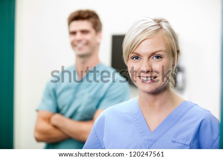 Portrait of young female vet in scrubs smiling with colleague standing in background