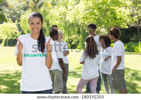 Portrait of young female volunteer gesturing thumbs up at park with friends in backgorund