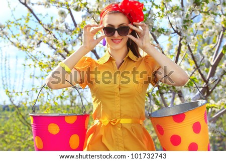 Portrait of young female with buckets on garden - stock photo