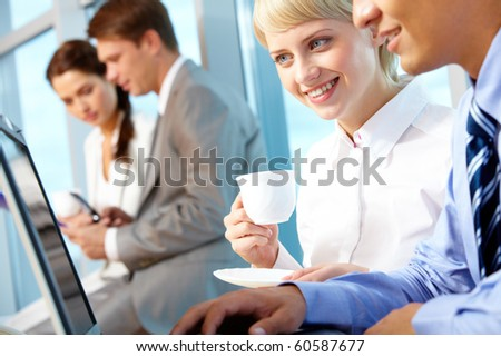 Portrait of young female with cup of coffee looking at laptop monitor in office and interacting with partner
