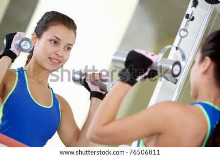 Portrait of young female with dumbbells doing exercises in gym in front of mirror