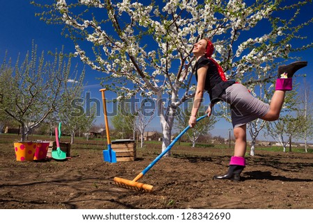 Portrait of young female with rakes on garden
