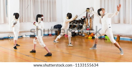 Portrait of young fencers with trainer engaged in fencing in training room
