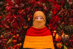 Portrait of young freckles girl wearing unusual stylish costume.  Little girl covered with three different colors scarves over ivy wall on background.