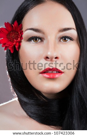 Portrait of young fresh beautiful healthy woman. red flower - stock photo