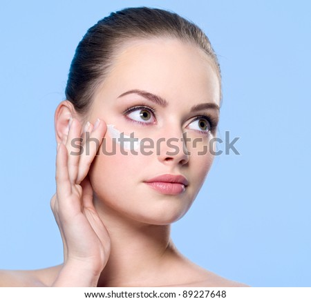 Portrait of young fresh woman applying cream on skin around  her eyes - blue background
