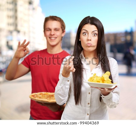 portrait of young friends holding pizza and potato chips at street