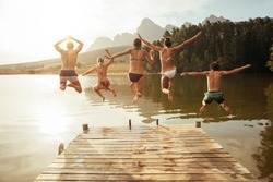 Portrait of young friends jumping from jetty into lake. Friends in mid air on a sunny day at the lake.