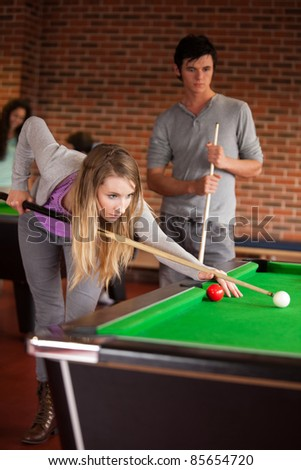 Portrait of young friends playing snooker in a student home