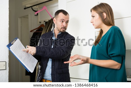 Portrait of young frustrated woman talking to debt collector visiting her at home and demanding to pay debts