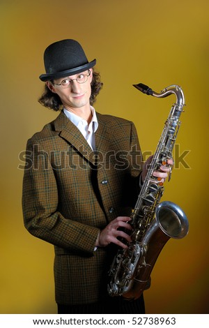 portrait of young funny man in bowler hat holding saxophone. yellow background