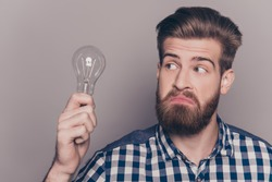 Portrait of young genious man with idea holding lamp.