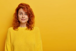 Portrait of young ginger woman has natural beauty, dressed in yellow knitted jumper, dimples at cheeks looks at camera with eyebrows raised, likes bright clothes. Warm tones. Copy space for text