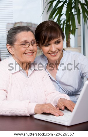 Portrait of young girl and her grandmother looking at laptop screen during work and smiling