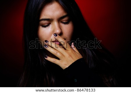 Portrait of young girl crying in the dark