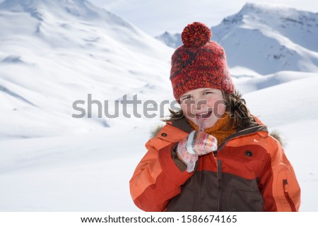 Portrait of young girl eating icicle on winter day