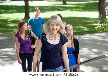 Portrait of young girl going to college with friends in background