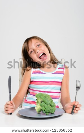 Portrait of young girl happy at meal time to eat her fresh vegetables, healthy eating concept