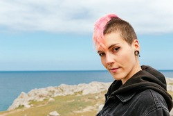 portrait of young girl in punk style. Woman with pink hair and piercings.